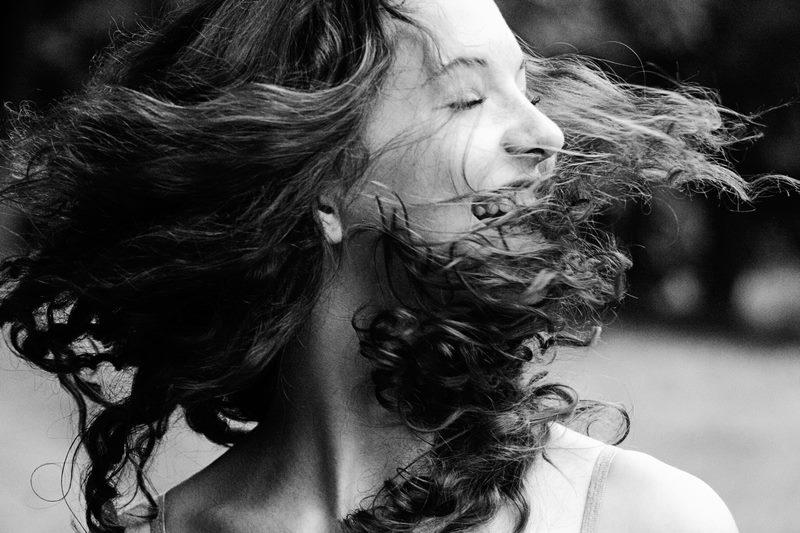 Eine junge Frau dreht sich mit fliegenden Haaren im Kreis.